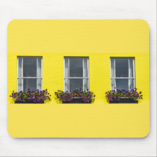 Three windows on a yellow wall mousepad