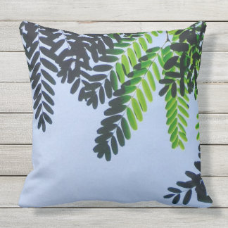 Throw pillow with green leaves on blue background
