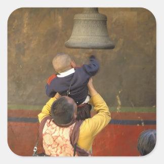 Tibetan Buddhist monk lifting a boy to ring a Square Sticker