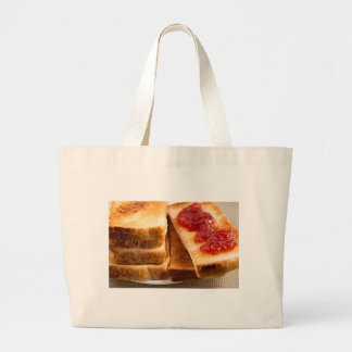 Toasted slices of bread with strawberry jam large tote bag