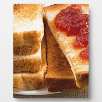 Toasted slices of bread with strawberry jam plaque