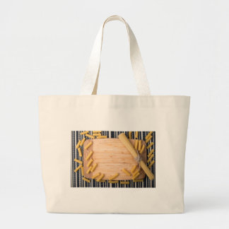Top view food background made of thin spaghetti large tote bag