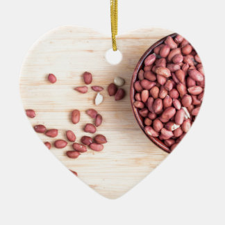 Top view of a brown bowl with raw peanuts ceramic heart ornament
