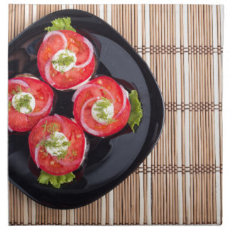 Top view of a dish with fresh sliced tomatoes napkin