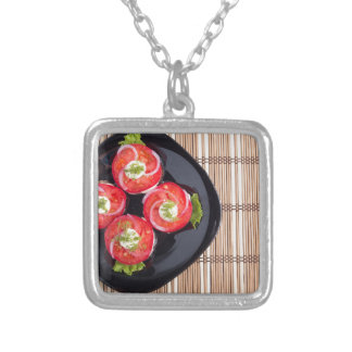 Top view of a dish with fresh sliced tomatoes silver plated necklace