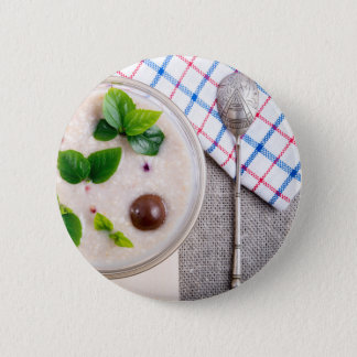 Top view of a healthy dish of oatmeal in a bowl 2 inch round button
