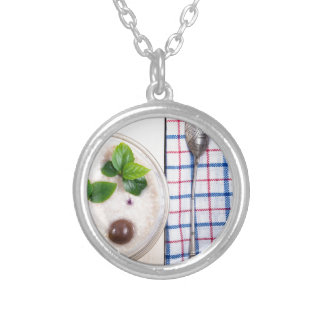 Top view of a healthy dish of oatmeal in a bowl silver plated necklace
