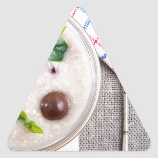 Top view of a healthy dish of oatmeal in a bowl triangle sticker
