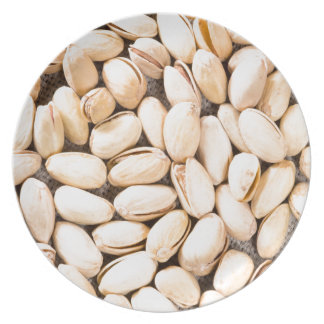 Top view of a lot of salty pistachios plate