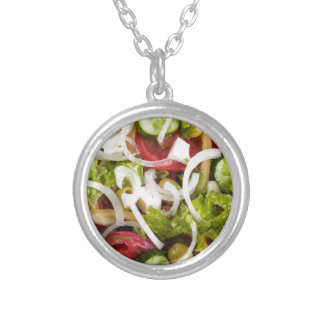 Top view of a plate of salad made from natural raw silver plated necklace