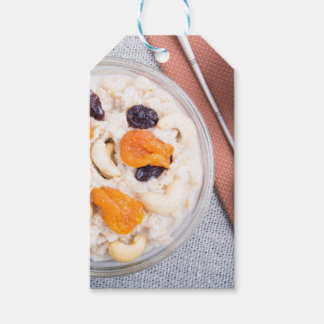 Top view of a portion of oatmeal with fruit gift tags