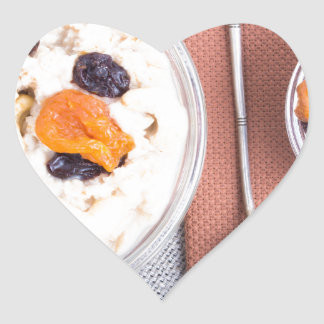 Top view of a portion of oatmeal with fruit heart sticker