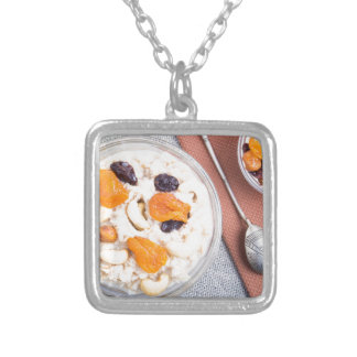Top view of a portion of oatmeal with fruit silver plated necklace