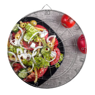 Top view of a small bowl of vegetables salad dartboard with darts