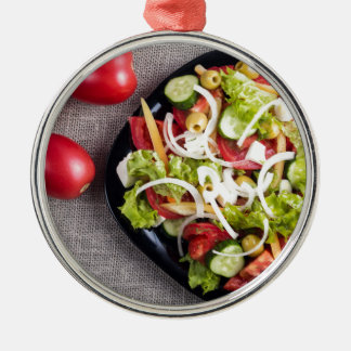 Top view of a small plate of raw salad Silver-Colored round ornament