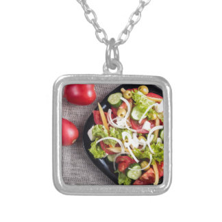 Top view of a small plate of raw salad silver plated necklace