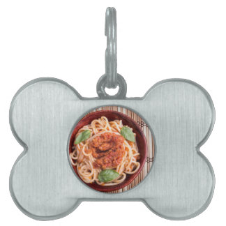 Top view of a thin spaghetti in a brown small wood pet tags