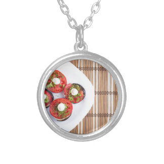 Top view of a vegetable dish of eggplant silver plated necklace