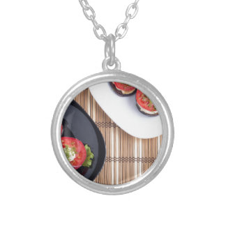 Top view of a vegetable dish silver plated necklace