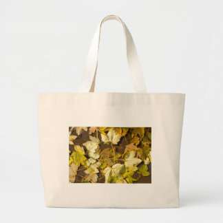 Top view of a wet autumn leaves large tote bag
