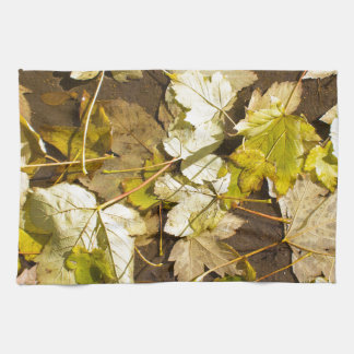 Top view of a wet autumn maple leaves kitchen towel