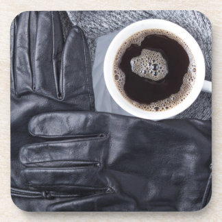 Top view of a white cup of coffee and black gloves coaster
