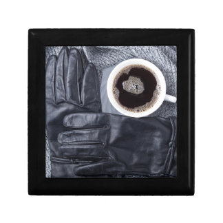 Top view of a white cup of coffee and black gloves gift box