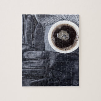 Top view of a white cup of coffee and black gloves jigsaw puzzle