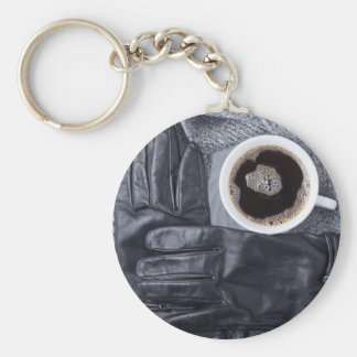 Top view of a white cup of coffee and black gloves keychain
