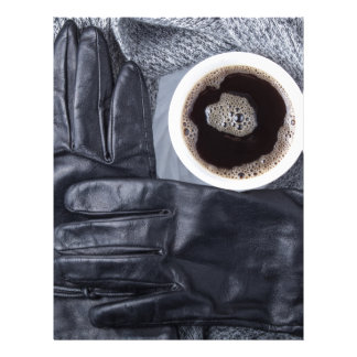 Top view of a white cup of coffee and black gloves letterhead