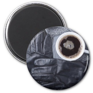 Top view of a white cup of coffee and black gloves magnet