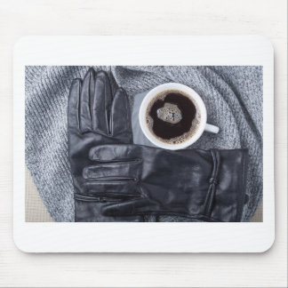 Top view of a white cup of coffee and black gloves mouse pad