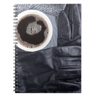 Top view of a white cup of coffee and black gloves notebook