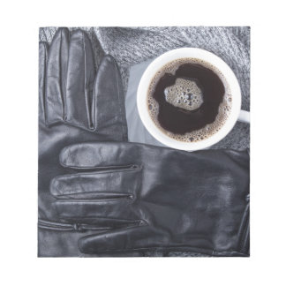 Top view of a white cup of coffee and black gloves notepad