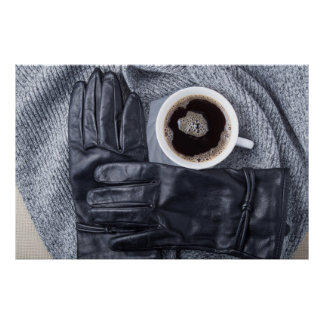 Top view of a white cup of coffee and black gloves poster