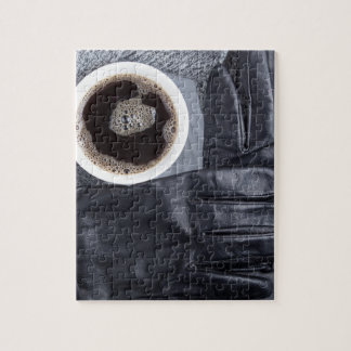 Top view of a white cup of coffee and black gloves puzzle