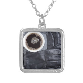 Top view of a white cup of coffee and black gloves silver plated necklace