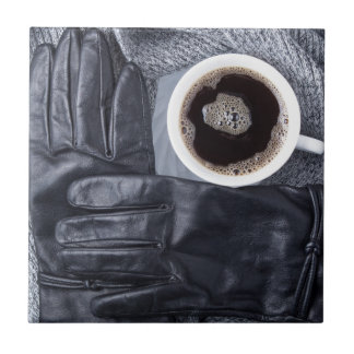 Top view of a white cup of coffee and black gloves tile