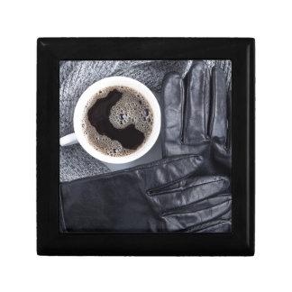 Top view of a white cup of coffee and gray woolen gift box