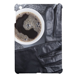Top view of a white cup of coffee and gray woolen iPad mini cover