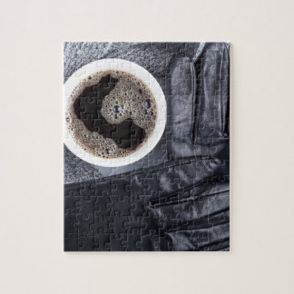 Top view of a white cup of coffee and gray woolen jigsaw puzzle