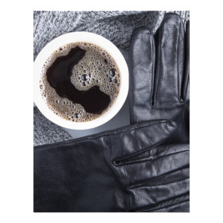 Top view of a white cup of coffee and gray woolen letterhead