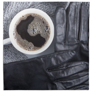 Top view of a white cup of coffee and gray woolen napkin
