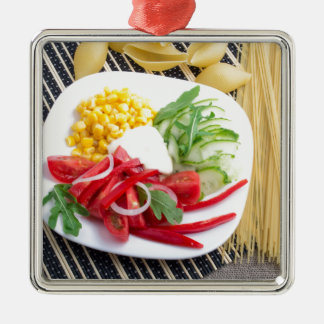 Top view of a white plate with salad Silver-Colored square ornament