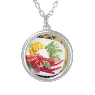 Top view of a white plate with salad silver plated necklace