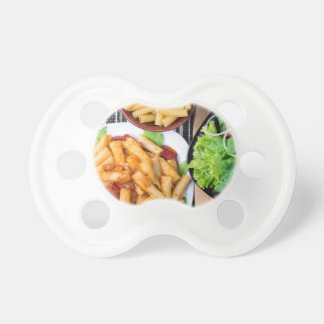 Top view of cooked rigatoni pasta with vegetables baby pacifier
