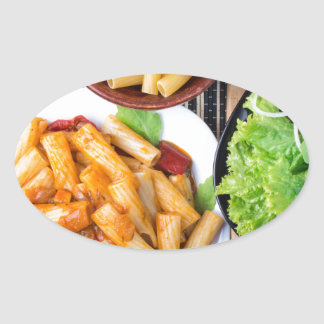 Top view of cooked rigatoni pasta with vegetables oval sticker