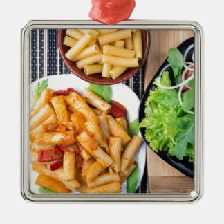 Top view of cooked rigatoni pasta with vegetables Silver-Colored square ornament