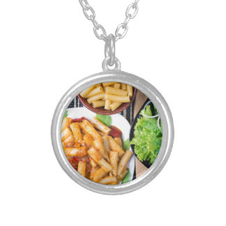 Top view of cooked rigatoni pasta with vegetables silver plated necklace