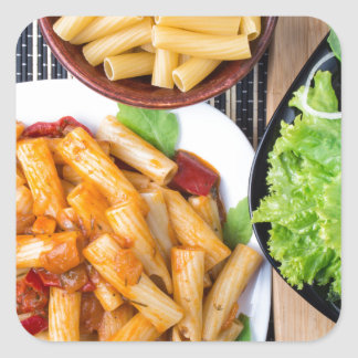Top view of cooked rigatoni pasta with vegetables square sticker